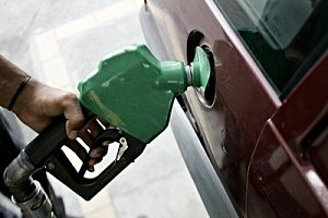 A pump attendant fills up a car with gas