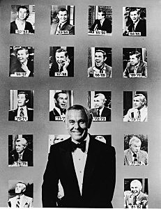 Johnny Carson Poses In Front Of Portraits